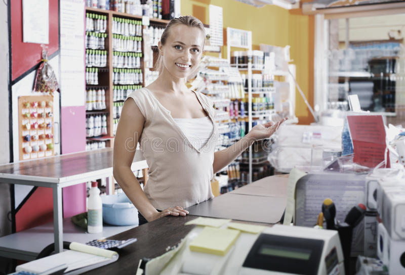 Young female seller standing at pay desk in supermarket royalty free stock image