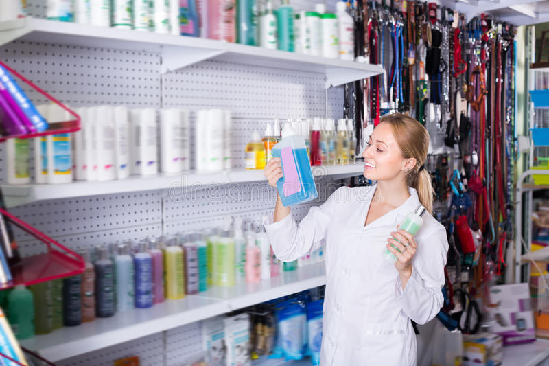 Young female shop assistant offering shampoo. For pets in pet shop royalty free stock photography
