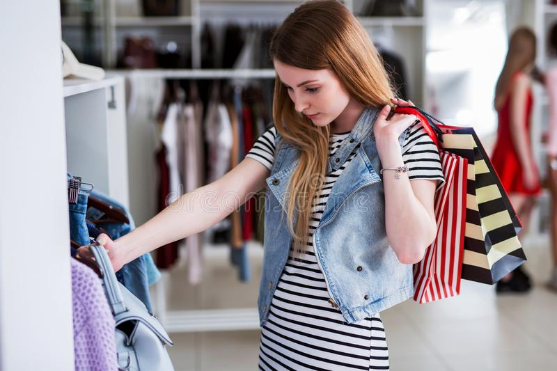 Young female shopaholic holding shopping bags and choosing ladies wear in clothing store royalty free stock images