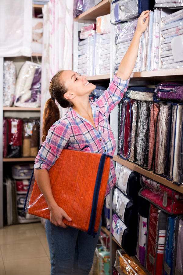 Young female shopper searching for bed linen. Pretty young female shopper searching for bed linen in textile shop royalty free stock photography