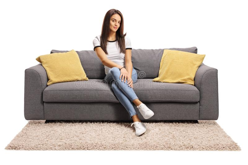 Young female sitting on couch with legs crossed stock photo