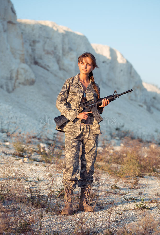 Young female soldier dressed in a camouflage with a gun in the l. Young beautiful female soldier dressed in a camouflage with a gun in the location stock images