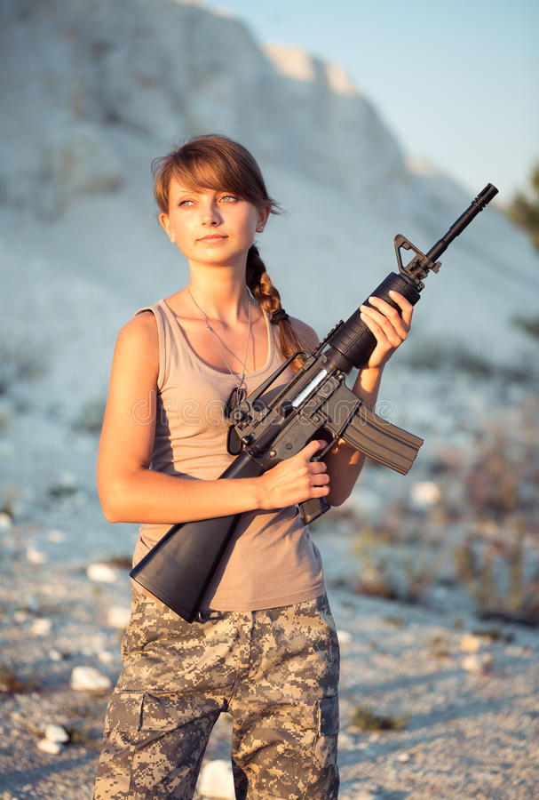 Young female soldier dressed in a camouflage with a gun in the o. Young beautiful female soldier dressed in a camouflage with a gun in the outdoor royalty free stock photos