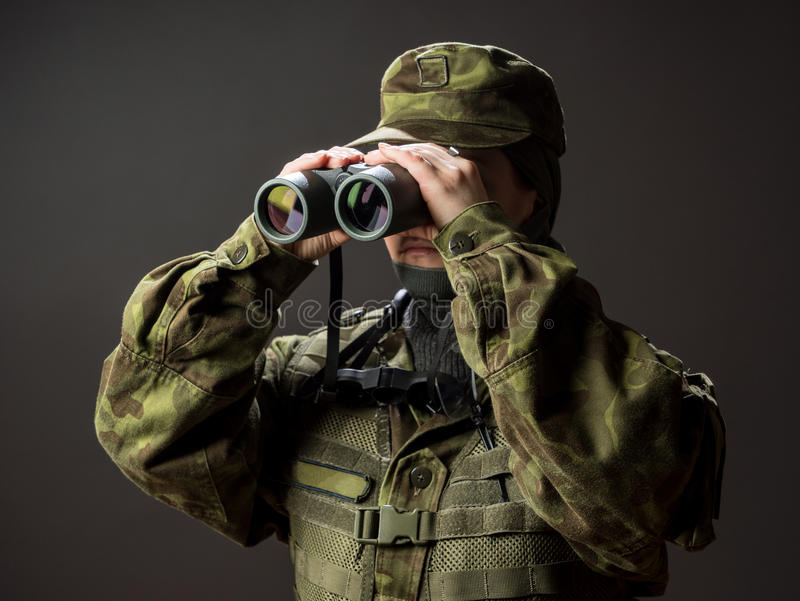 Young female soldier observe with binoculars. War, military, army people concept stock image