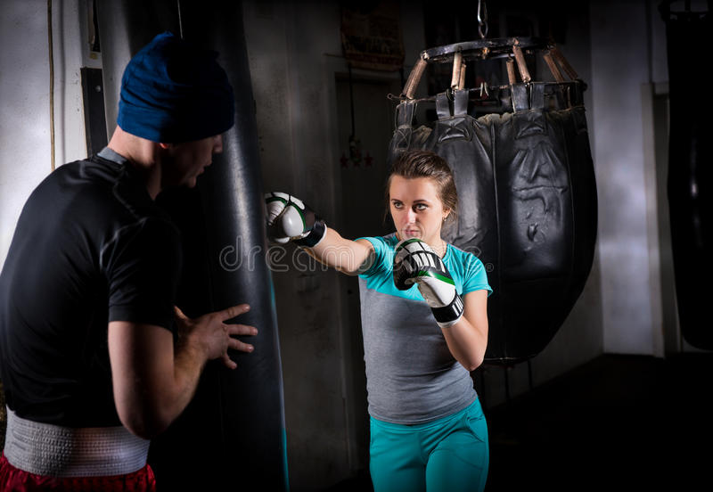Young female sporty boxer in boxing gloves training with her couch and boxing punching bag stock photo