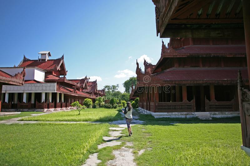 A young female stands by the ornately decorated central red palace complex in Mandalay stock image