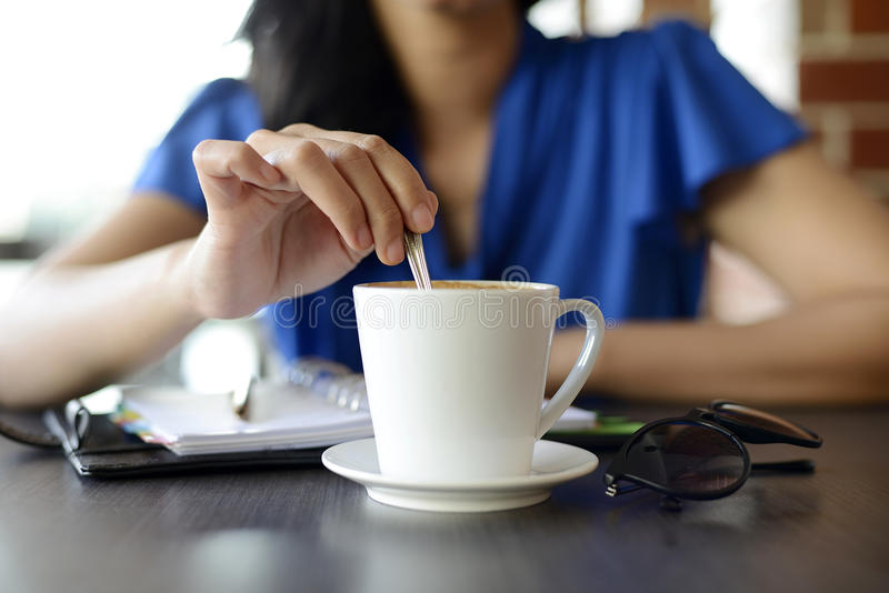 Young female stir cup. Of coffee in the morning at Cafe stock image
