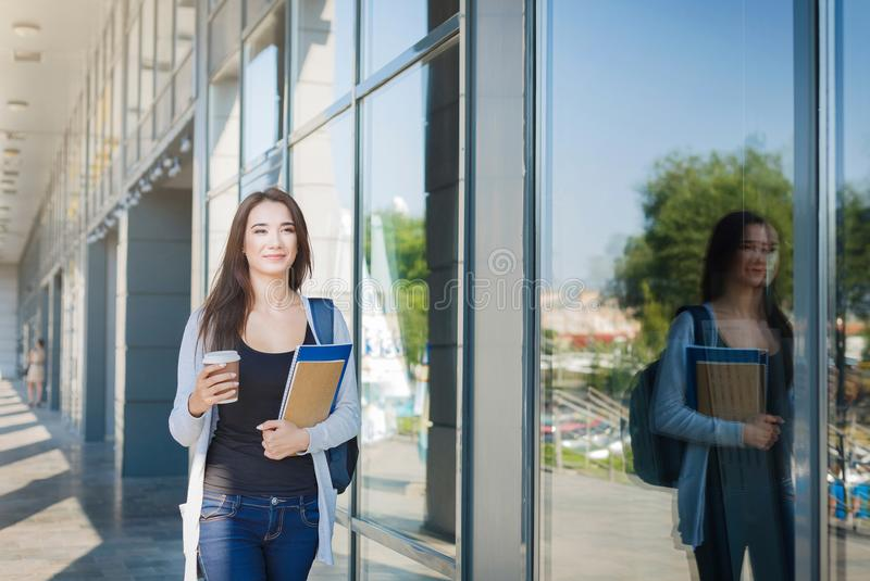 Young female IT student, with books and backpack. Going to lecture and drinking coffee stock photo