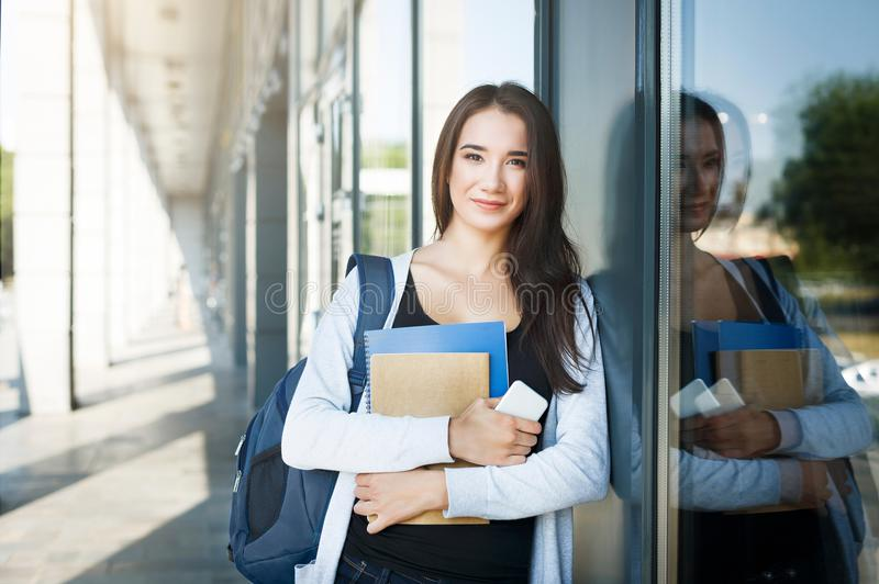 Young female IT student, with books, smartphone and backpack. Staying outside before lesson and smiling royalty free stock image