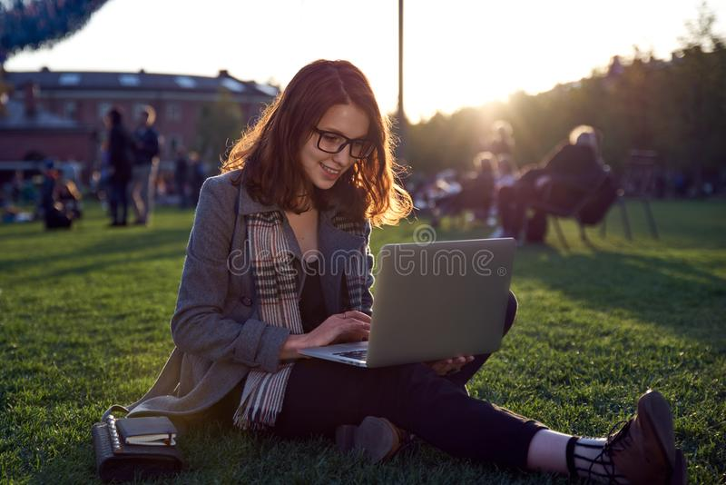 Young female student doing homework on laptop sitting on green grass in the Park. Red long hair and glasses. Concept training, bus stock photos