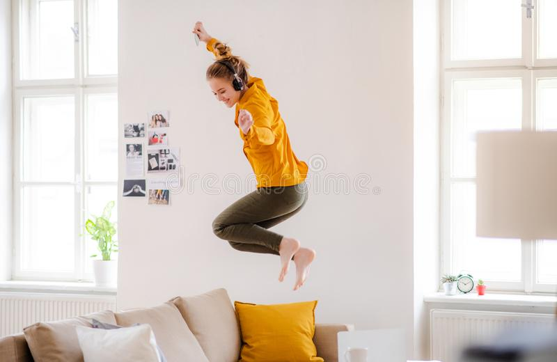 A young female student with headphones jumping on sofa when studying. A young female student with headphones and telephone having a break when studying, jumping stock images
