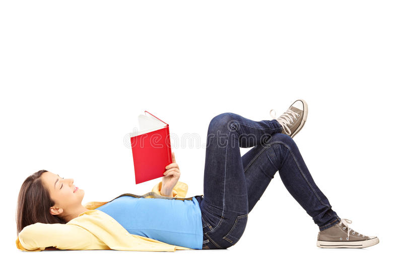 Young female student lying on a floor and reading a novel stock images