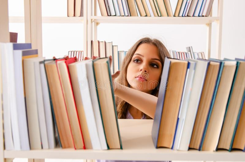 Young female student preparing for exams at library stock photography