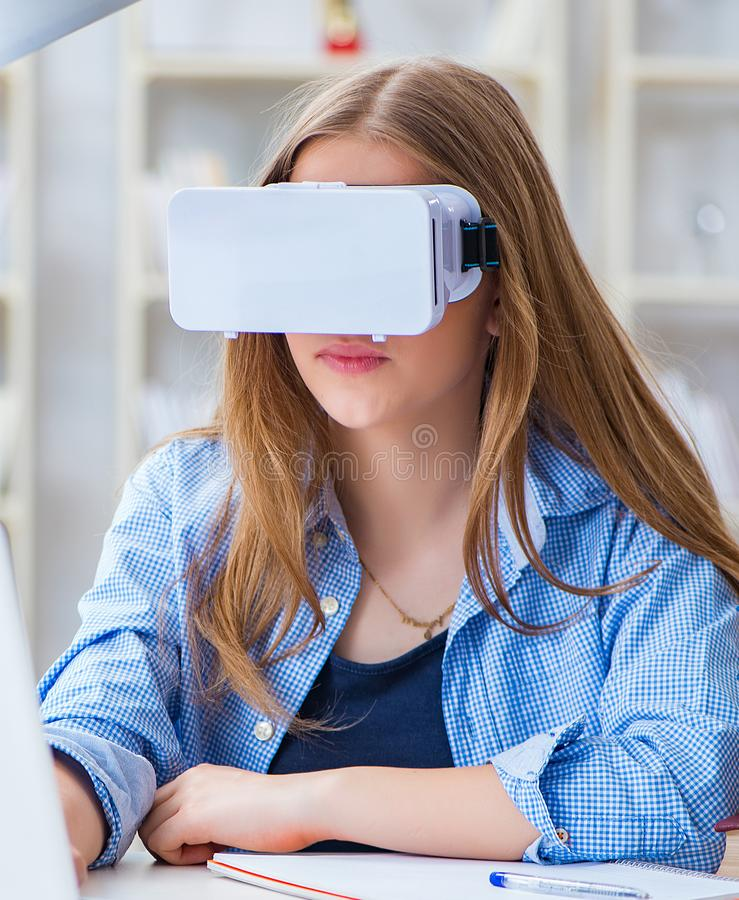 Young female student preparing for exams with VR glasses stock photos