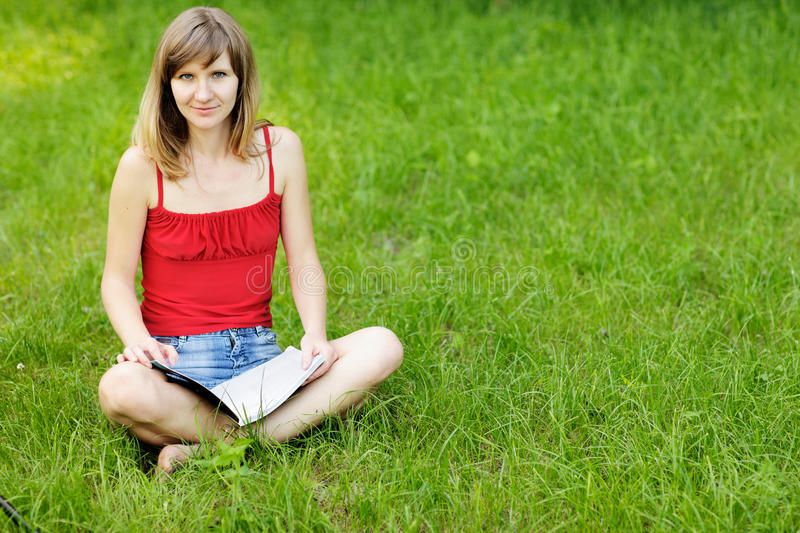 Young female student reading on nature royalty free stock photos