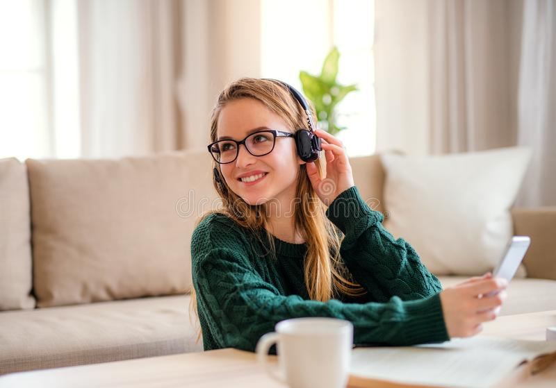 A young female student sitting at the table, using headphones when studying. A young happy college female student sitting at the table at home, using headphones stock photos