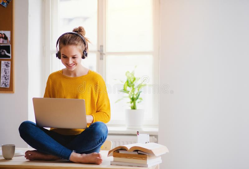A young female student sitting at the table, using headphones when studying. A young happy college female student sitting at the table at home, using headphones stock image