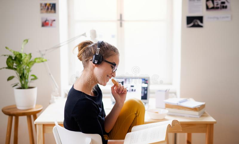 A young female student sitting at the table, using headphones when studying. A young happy college female student sitting at the table at home, using headphones royalty free stock image