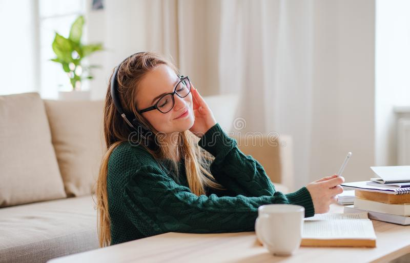 A young female student sitting at the table, using headphones when studying. A young happy college female student sitting at the table at home, using headphones stock photo