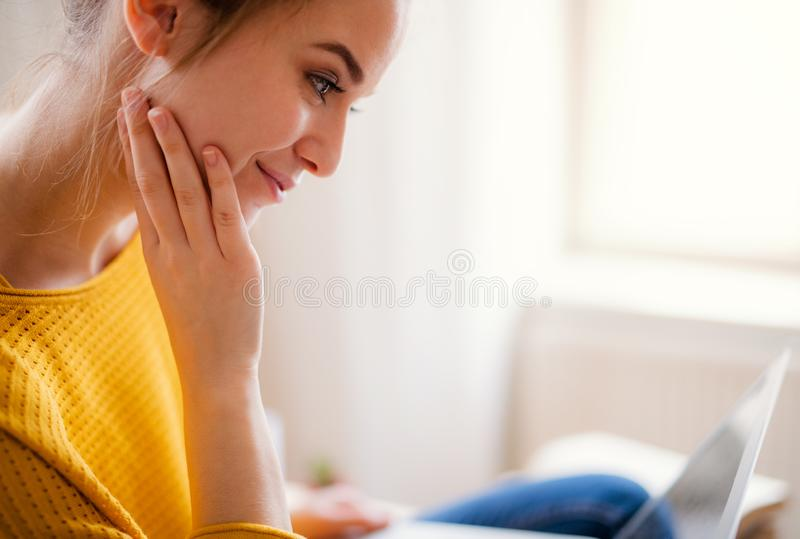 A young female student sitting at the table, using laptop when studying. A young happy college female student sitting at the table at home, using laptop when royalty free stock images