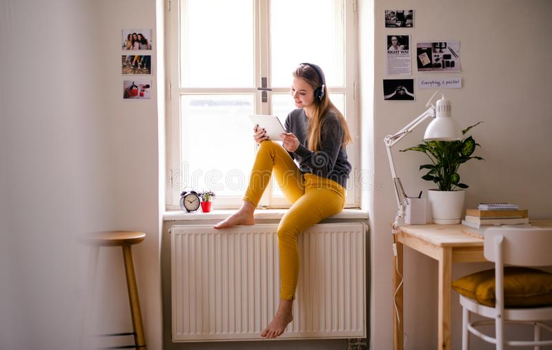 A young female student sitting on window sill, using tablet when studying. A young happy college female student sitting on window sill at home, using tablet and stock photo