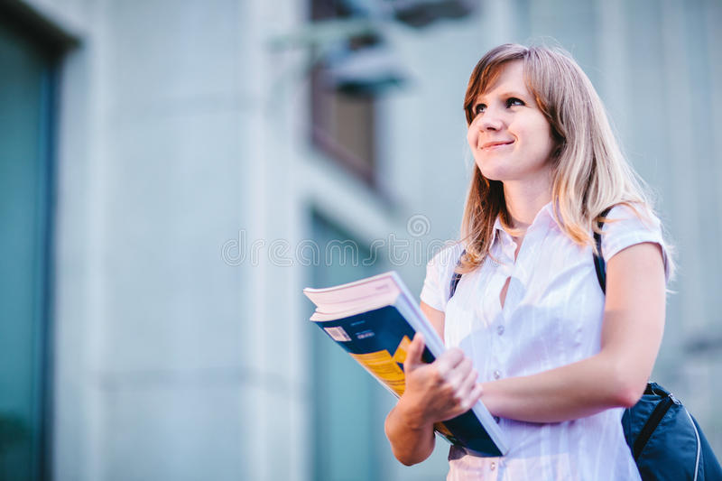 Young female student standing near university holding books royalty free stock images