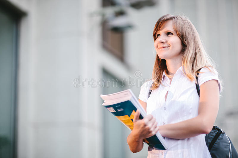 Young female student standing near university holding books stock photo