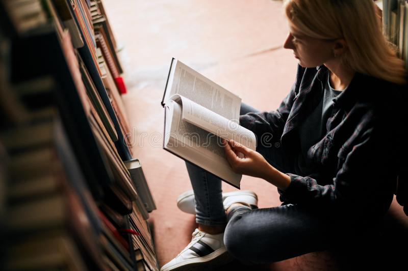 Young female student studying in the library Higher education. Student life. Young female student with long blonde hair and earbuds finds smth interesting royalty free stock image