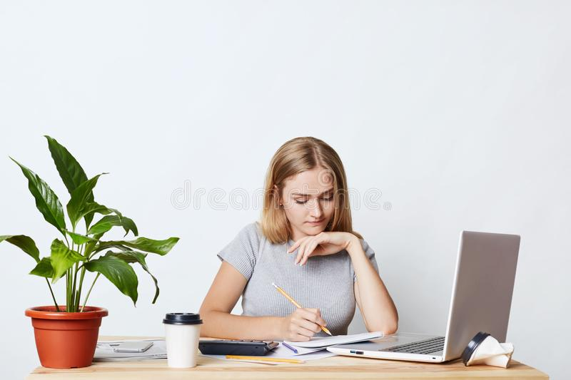 Young female student studying math, preparing report, making notes from laptop, writing in her copy book, isolated over white back stock photography