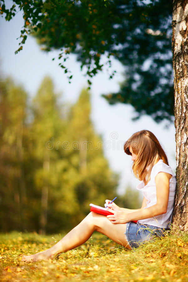 Young female student studying outdoors in the autumn. royalty free stock photos
