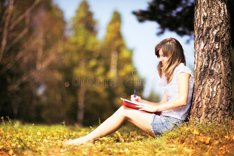 Young female student studying outdoors in the autumn. stock photo