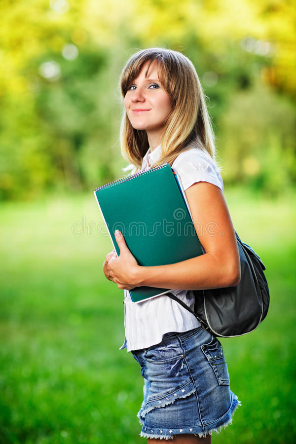 Young female student with workbook standing on green blurred grass background.  stock photo