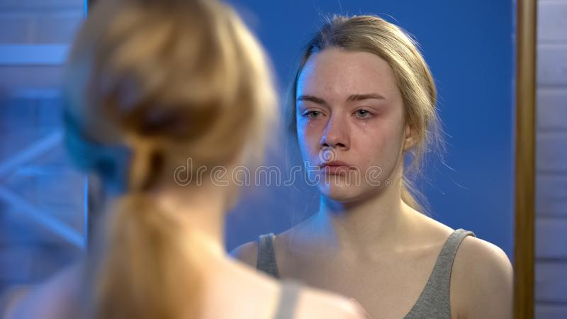 Young female suffering depression, crying looking at mirror reflection, despair stock images
