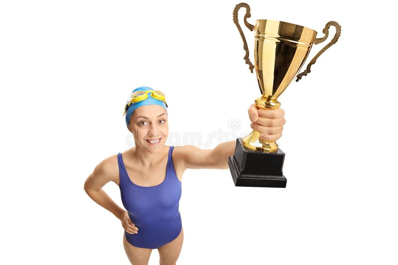 Young female swimmer holding a gold trophy royalty free stock photos