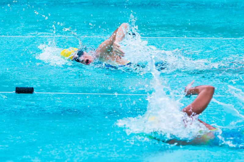 young female swimmers race in freestyle stroke at a school swimming pool in Chiang Mai, Thailand royalty free stock image