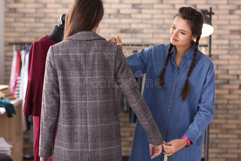 Young female tailor working with client at the final fitting in atelier royalty free stock photography