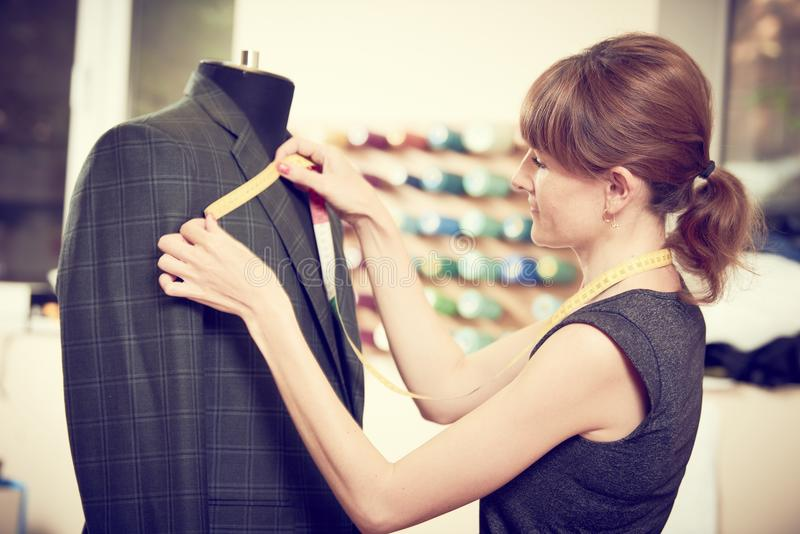 Female tailor works with male suit stock photo