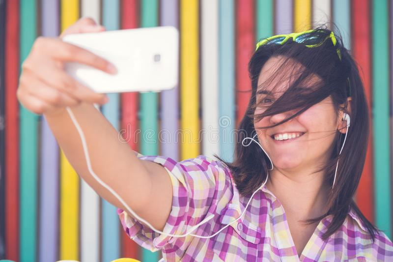 Young female taking selfie in front of colorful wooden wall stock image