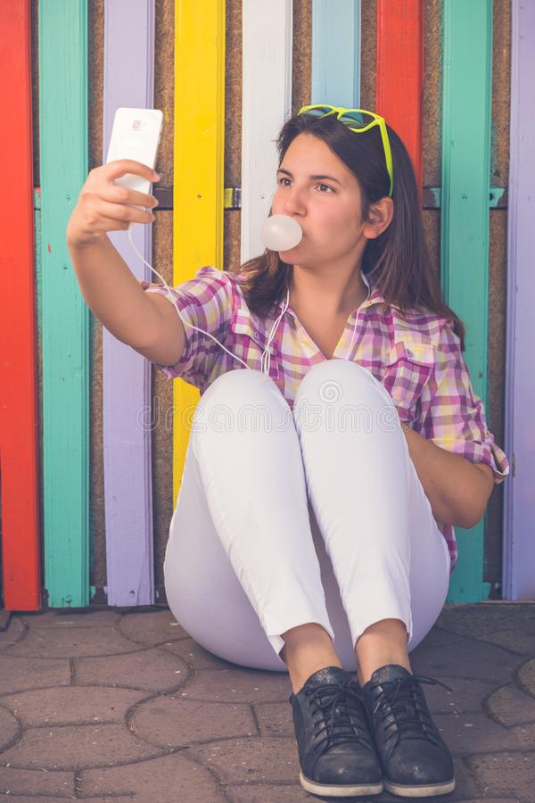 Young female taking selfie in front of colorful wooden wall royalty free stock photos