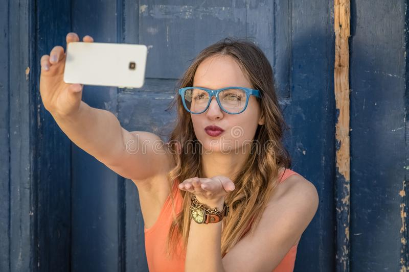 Young female taking selfie in front of old door royalty free stock images