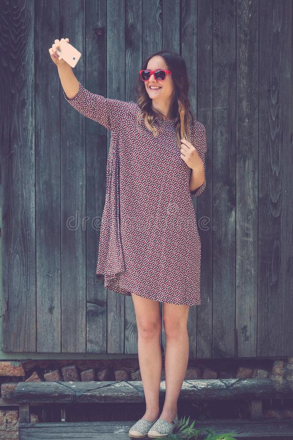 Young female taking selfie with smartphone against wooden wall. Beautiful young female taking selfie with smartphone on old wooden wall background. Fashion and stock photos