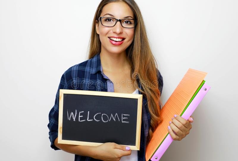 Young female teacher holding folders and blackboard with written welcome.  stock photo