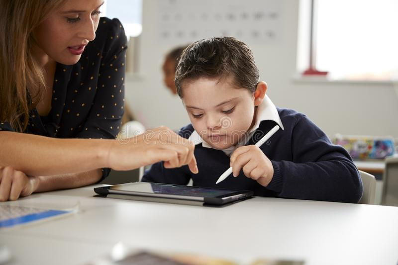 Young female teacher working with a Down syndrome schoolboy sitting at desk using a tablet computer in a primary school classroom,. Front view, close up stock photo