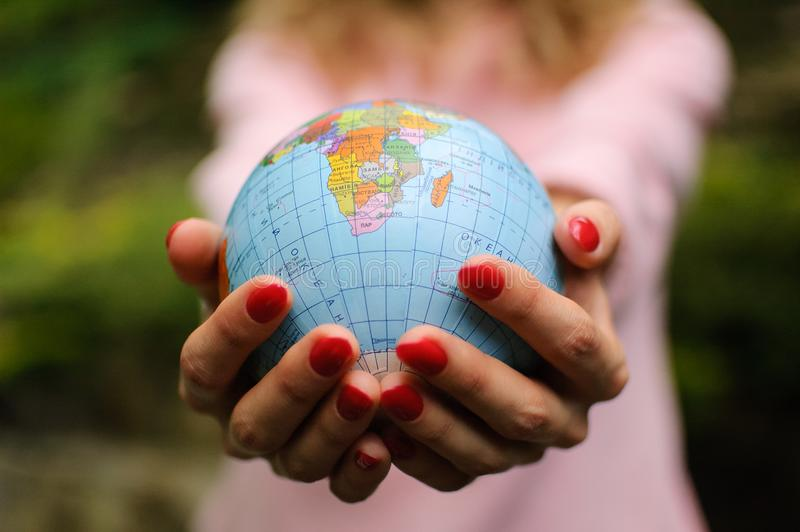 Young female teenager in pink casual clothes with red manicure holding a little globe in her hands. Enviromental. Responsibility concept royalty free stock image