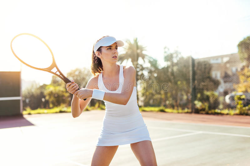 Young female tennis player outdoor playing stock photography