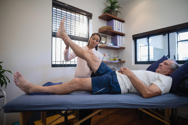 Young female therapist examining leg of senior male patient lying on bed stock photography