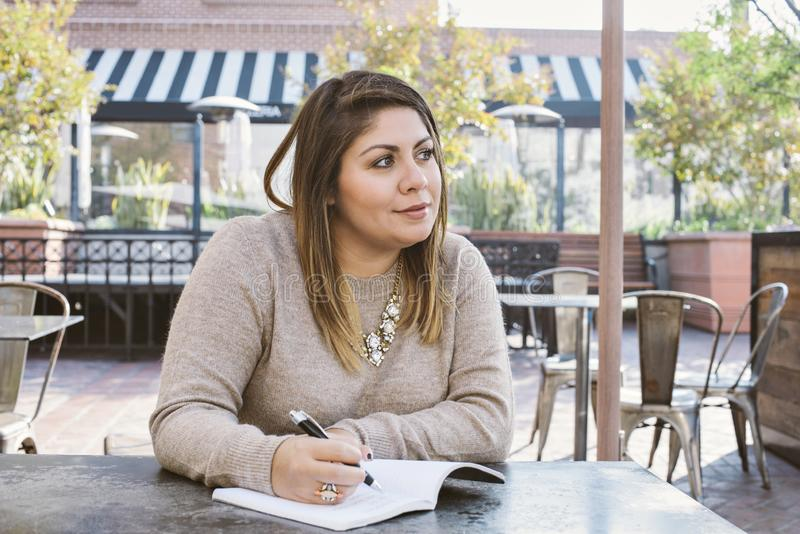 Latina Woman Writes Down in a Journal at a Coffee Shop royalty free stock photos