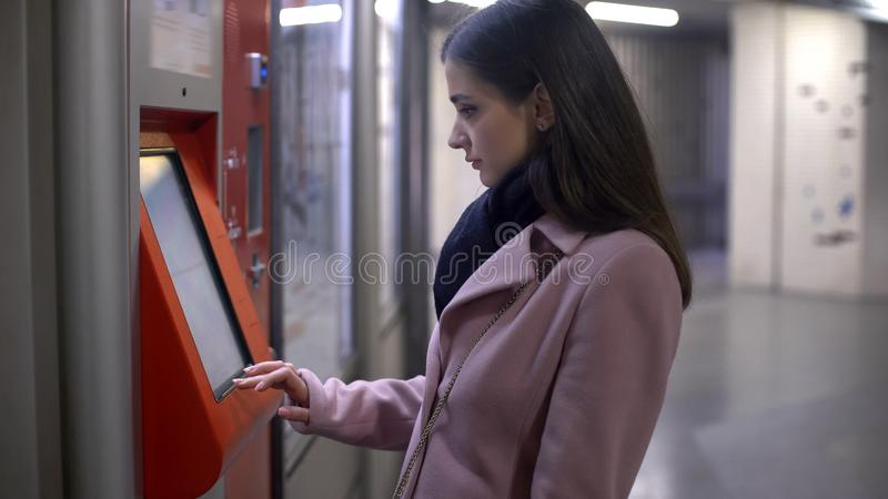 Young female tourist buying tickets in self-service terminal, making payment stock image