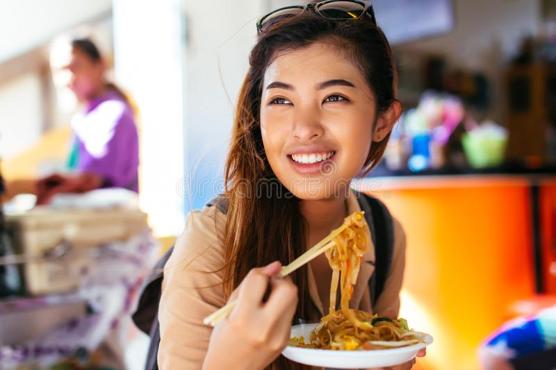 Young female tourist eating pad thai noodle at the shop royalty free stock photography