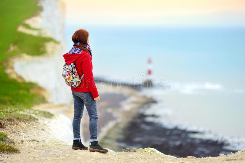 Young female tourist enjoying beautiful view of white chalk cliffs of the Seven Sisters at Birling Gap coastline, Eastbourne, UK royalty free stock photography